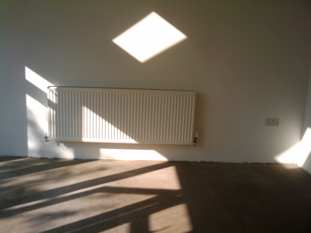 A sunny room and a very large radiator