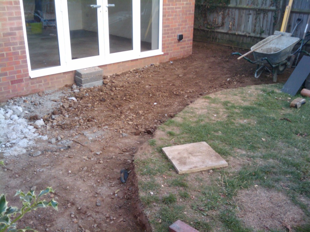 The curve of the patio will be with red bricks, with a light paving stone. It will slope down to the drain