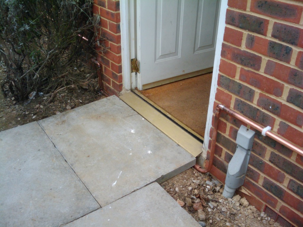 Copper pipes running under the front door threshold - need to de-wobble the paving stone though